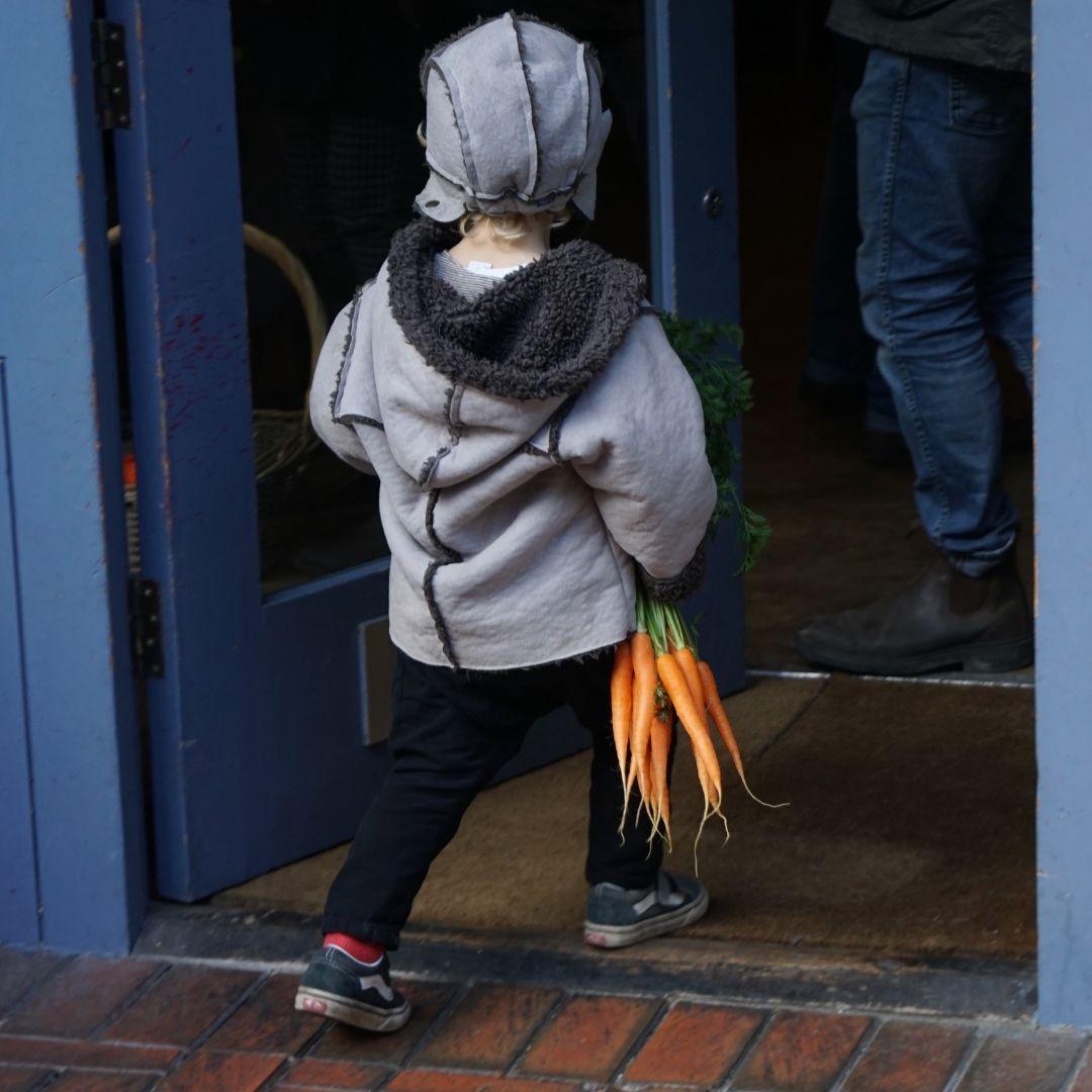 dziecko z pęczkiem marchewki